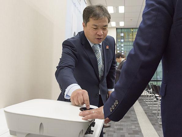 来場者に製品を説明する西村氏。コンパクトで設置が容易な点も同社パワコンの特長である